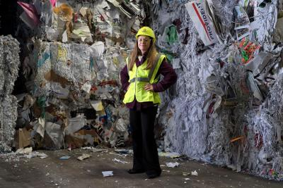 Beth MacKenzie standing in front of recycleable materials