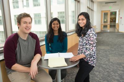 three undergraduates sitting in research facility