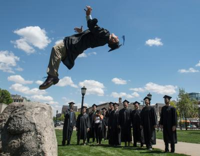 graduate leaping off rock while others watch
