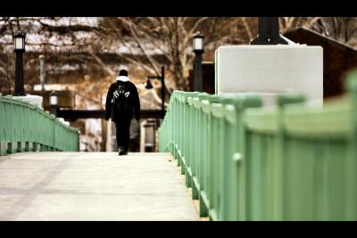 A young man walks across a bridge.