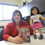 Dawn Bowlus with an American Girl Doll and educational curriculum that she helped develop.