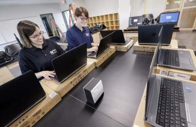 Jenna Whipple and Amanda Anderson with RTI setup laptop computers that will go on a laptop cart as preparations continue at the Kirkwood Center at the University of Iowa in Coralville, Iowa, on Wednesday, August 12, 2015.