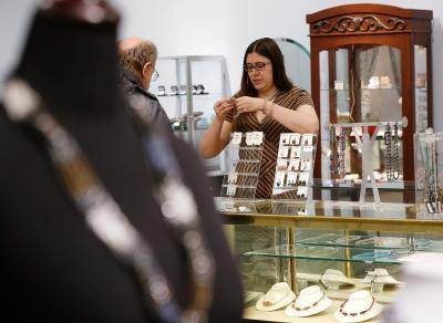 Owner Abby Restko shows a necklace to a customer in her store, Glassando, in its new, larger location in the Old Capitol Mall in Iowa City on Monday, Jan. 11, 2016.
