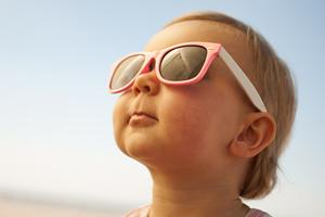 A baby in sun glasses looks up at the sky.