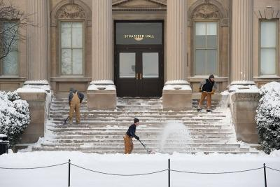 Members of Landscape Services shovel away snow from a UI building.