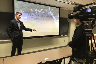 student speaking with reporter during presentation