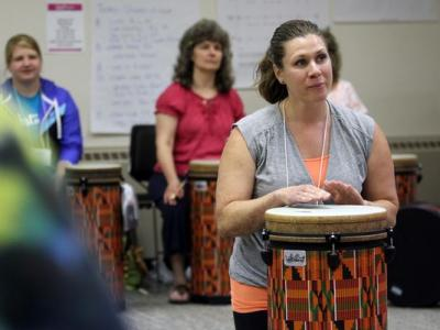 Becky Schmitz leads a group during a drumming workshop at the Iowa Memorial Union on Thursday, July 16, 2015.