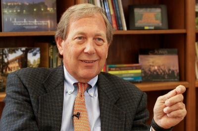 Close-up of Bruce Harreld speaking in front of bookcase