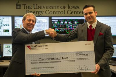 two men shaking hands and holding a check