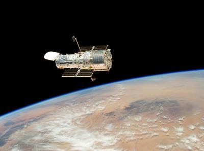 Hubble Telescope floating above Earth.