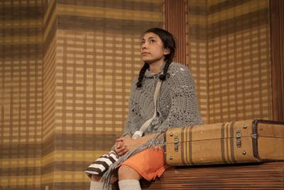 The protagonist in The Maleta sits next to her suitcase.