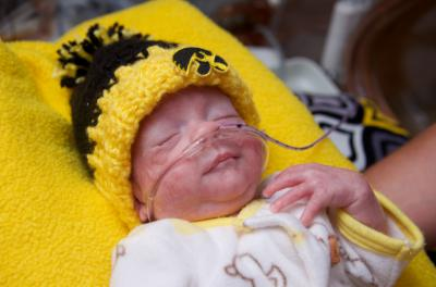 pre term infant wearing knitted black and gold hawkeye hat