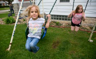 A little girls swings on a swing set