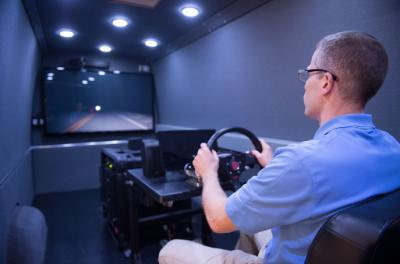 a participant inside the miniature version of the University of Iowa's advanced driving simulator
