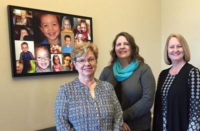 women standing before bulletin board with children's photos
