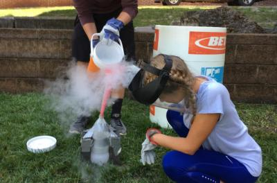 students pouring nitrogen into trashcano