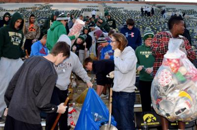 students cleaning up football stadium seats