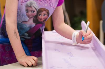 Xela Weber, 6, of Galena, Ill., signs her name to a special purple beam set aside just for patients and families of University of Iowa Children's Hospital