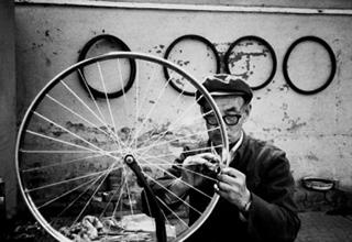 A Chinese man holds a bicycle wheel.