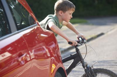 young boy crossing road on bike