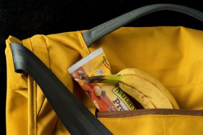 Bookbag with breakfast bar and banana spilling out of it.