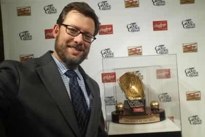 sean forman posing before gold glove trophy