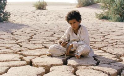 Film still of boy sitting on dry land from movie THEEB