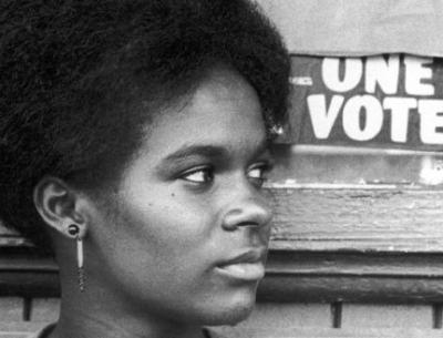 a black woman stands by a One Vote sign