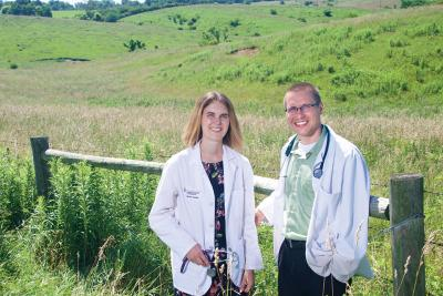two medical professionals standing by green field