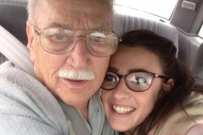 young woman and her grandfather embracing in car