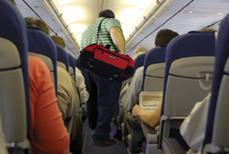 A large man carrying a red gym bag walks down an airplane aisle.