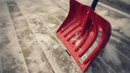 A red shovel moving snow