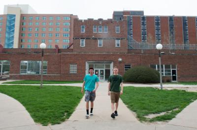 Students walking with three residence halls shown in the background