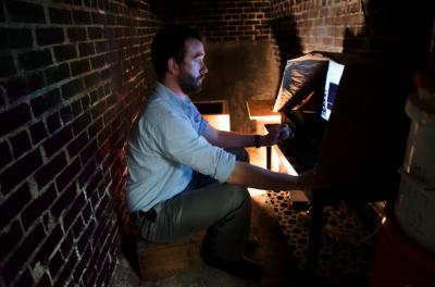 man monitoring seismometer in basement room