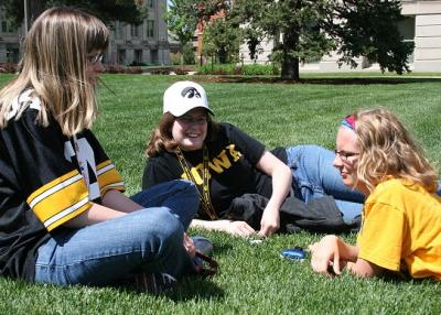 Image of 3 UI students lounging on the UI Pentacrest lawn