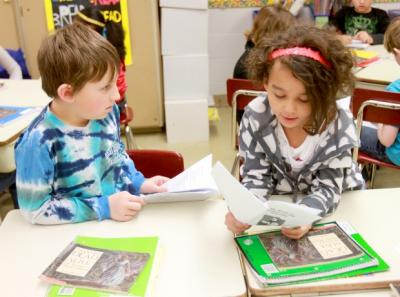 Jane Addams Elementary School third-graders Carter Morrell, 9, and Kadene Tatum, 9, work on reading together. Quad-City Times photo by Larry Fisher