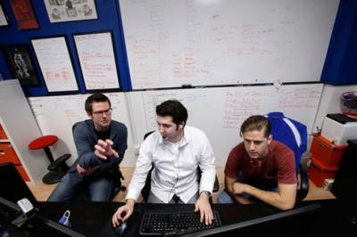 Three guys, Cofounder, CEO and quarterback John Schnipkoweit, (left), cofounder and commissioner of code Chris Quartier, cofounder and game master Nick Sihacek work in the office of RecBob in downtown Cedar Rapids. (Cliff Jette/The Gazette)