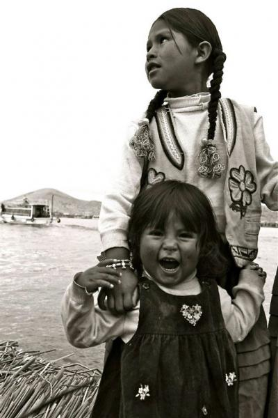 3 year old Kusyia is guarded by her sister. The Quechuan girls live on the floating islands of Lake Titicaca, Peru.