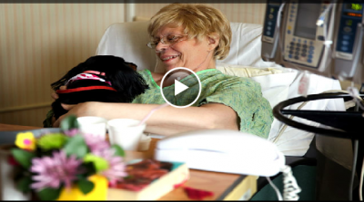 A woman cuddles a dog while a patient in a hospital