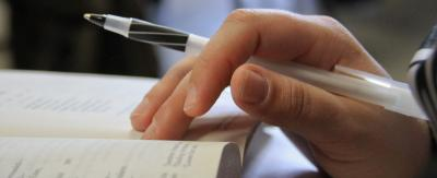 An image of writer holding a pen with an open journal