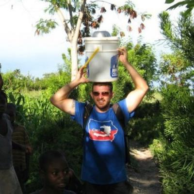 UI alumnus Shaun Harty balances a pail on his head while delivering healthcare in Haiti