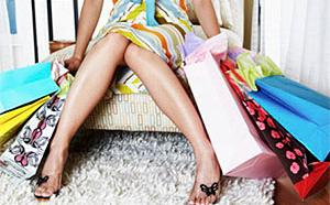 An image of a woman's torso sitting on a chair surrounded by shopping bags in a story on compulsive shopping