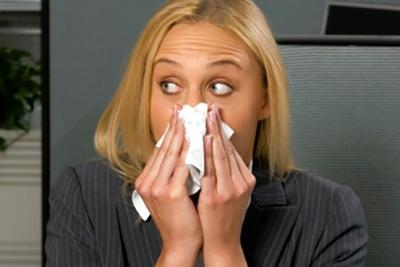 A woman blows her nose into a Kleenex