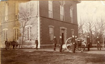 Historic photo of soldiers with cannon on central campus