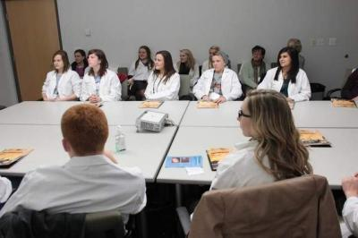 High school students listen to University of Iowa junior Sergio Loubriel during a presentation Thursday at the Medical Education and Research Facility. The session was one of numerous laboratory tours offered to students interested in pursuing a career in