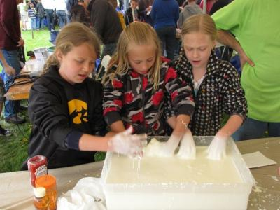 Elise Finn, 9, Aricka Ramser, 10, and Olivia Harmon, 10, all of Muscatine, discover what the oobleck feels like, which is liquid made of cornstarch and water