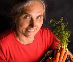 Dr. Terry Wahls holds a bin full of brightly colored vegetables and fruits
