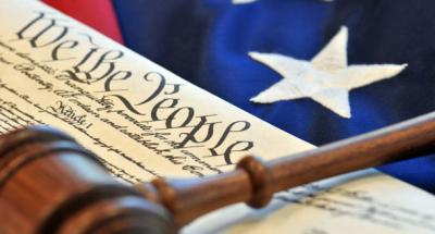 Color photo of a gavel, U.S. Constitution, and American flag