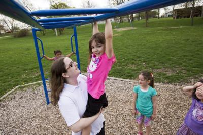Brittany Honer helps her daughter, Kaitlin Ansell, 5, across the monkey bars at Jacolyn Park on Tuesday, May 7, 2013, in Cedar Rapids. A U.S. Census Bureau reports a big spike among unwed mothers in the 20 to 24 age range, which includes Honer, 22. (Liz M