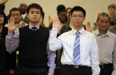 George Chen (left) from Taiwan and his brother Henry Chen stand and place their hands as they swear the Oath of Allegiance to the United States during a naturalization ceremony at the Federal Courthouse for the Northern District of Iowa on Nov. 16, 2012,